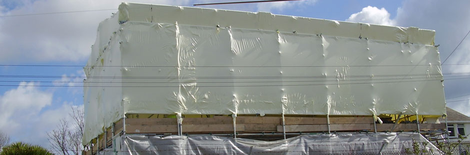 Photo of building with scaffolding and shrink wrap encapsulation in place protecting the structure